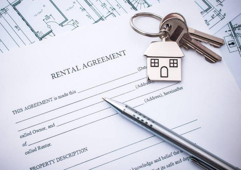 A imagem mostra um contrato de aluguel sobre um planta de imóvel. No canto superior direito, duas chaves prateadas num chaveiro em formato de casa. No canto inferior direito, uma caneta prateada.
